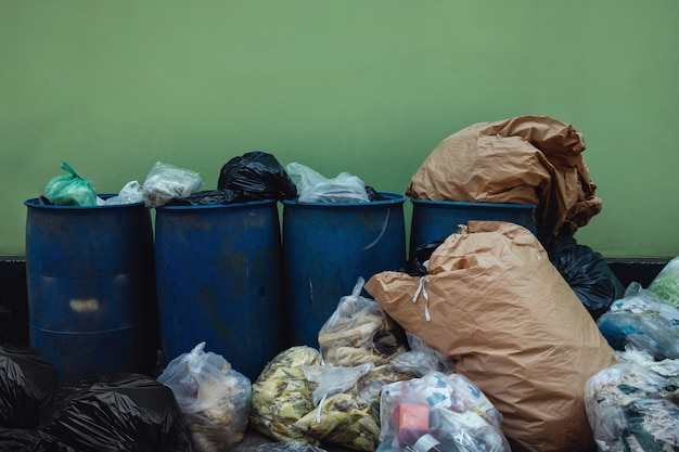 Veel garbages en vuilnis tegen de muur.