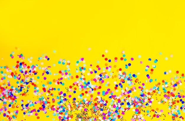 Veel gekleurde confetti op een gele achtergrond.