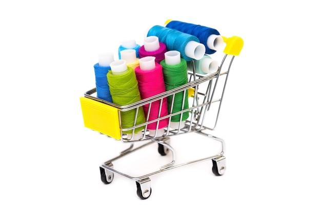Veel gekleurde draden in een winkelwagentje op een wit oppervlak