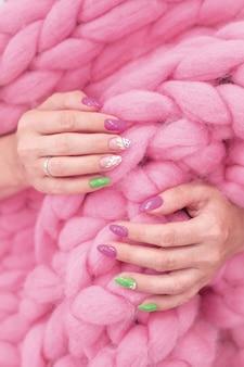 Veel gekleurde, glanzende manicurehanden hebben verschillende roze vlekken