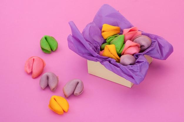 Veel gekleurde koekjes in de vorm van schelpen op een roze achtergrond en een doos