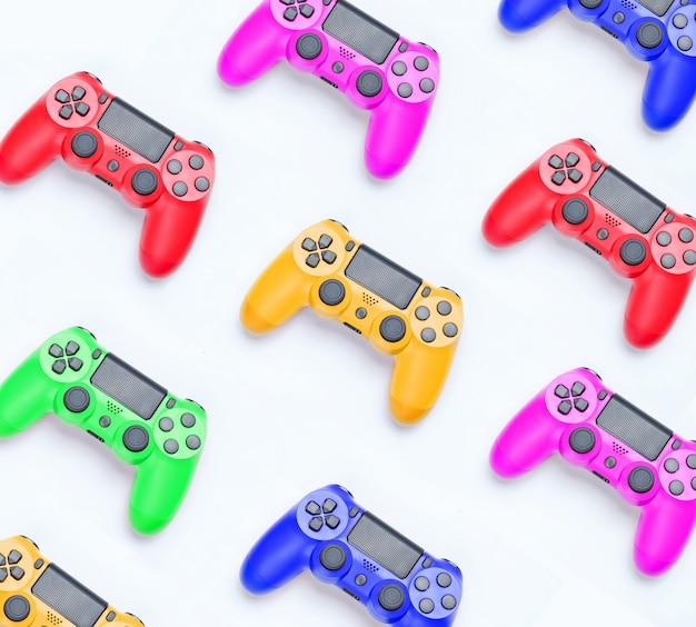 Veel gekleurde plastic gamepads op een grijze achtergrond. individualiteit van het concept.
