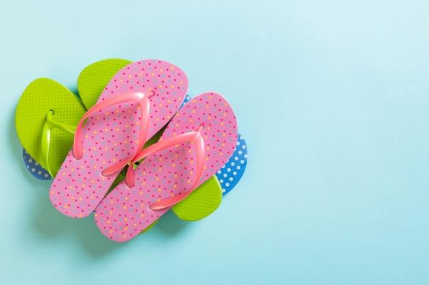 Veel gekleurde slippers op blauw.