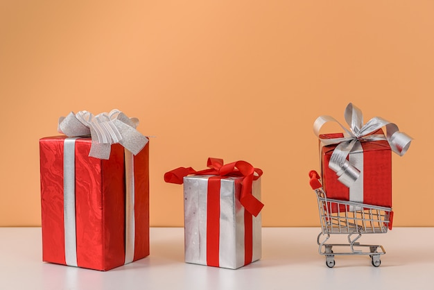 Veel geschenkdoos met rode strik en winkelwagentje of trolley op witte tafel en pastel oranje muur
