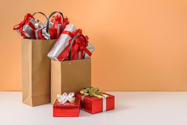 Veel geschenkdoos met rode strik in bruine papieren boodschappentas. concepten nieuwjaarsgeschenk of kerstmis