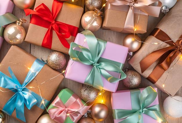 Veel geschenkdozen met gekleurde linten en kerstballen. bovenaanzicht. vrolijk kerstfeest en een gelukkig nieuwjaar.