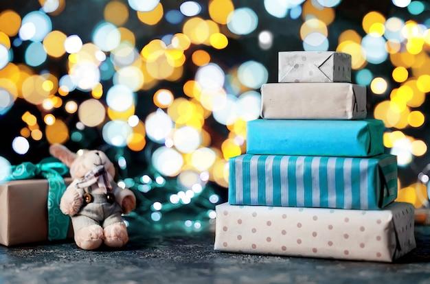 Veel geschenken in inpakpapier ambachtelijke en zelfgemaakte peperkoek huis, lichten bokeh op donkere achtergrond,