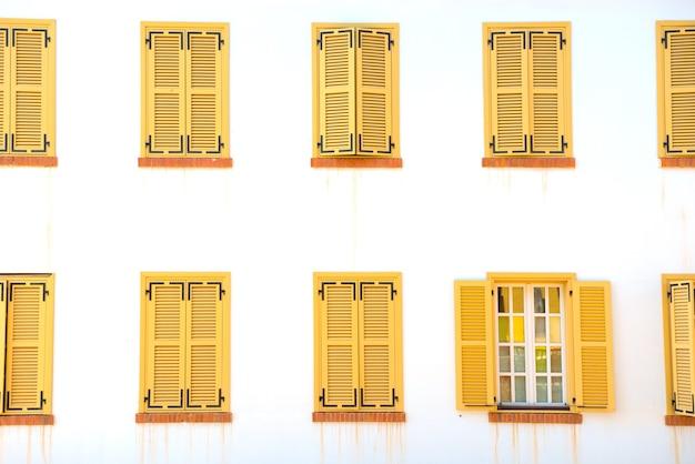 Veel gesloten ramen met luiken op de witte muur