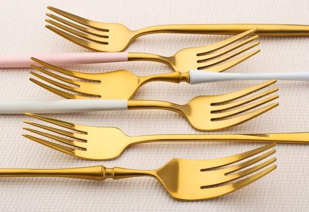 Veel gouden vorken op een lichte tafel. gouden set vorken