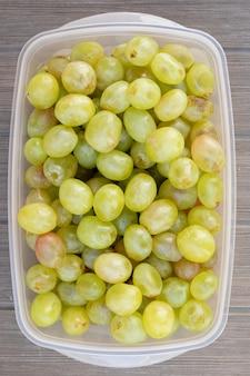 Veel groene druiven in een plastic doos