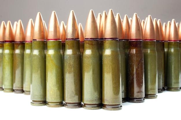 Veel groene en een bruine 7,62 mm patronen voor kalashnikov aanvalsgeweer