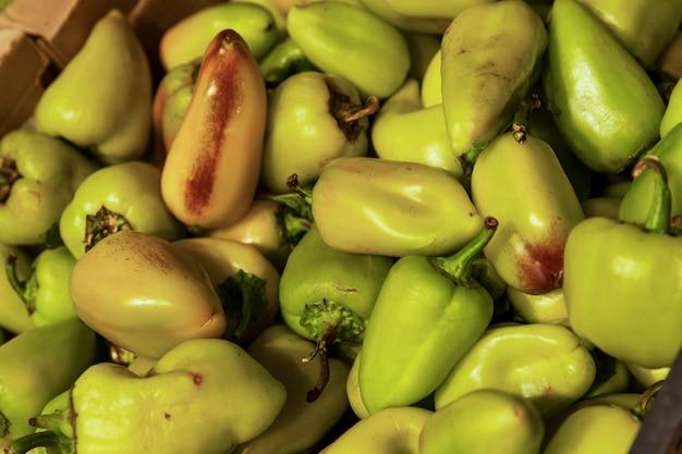 Veel groene paprika's in de winkel. vitaminen en gezondheid uit de natuur. detailopname.