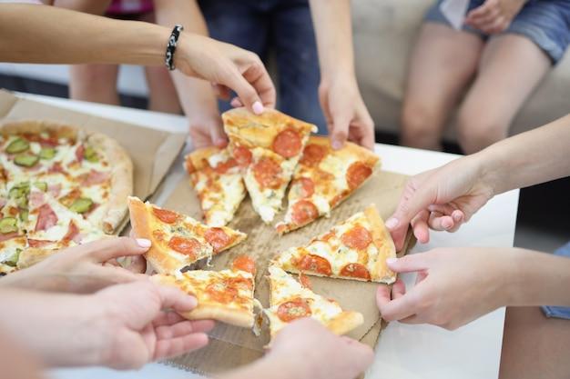 Veel handen van volwassenen en kinderen die plakjes heerlijke smakelijke pizza close-up nemen