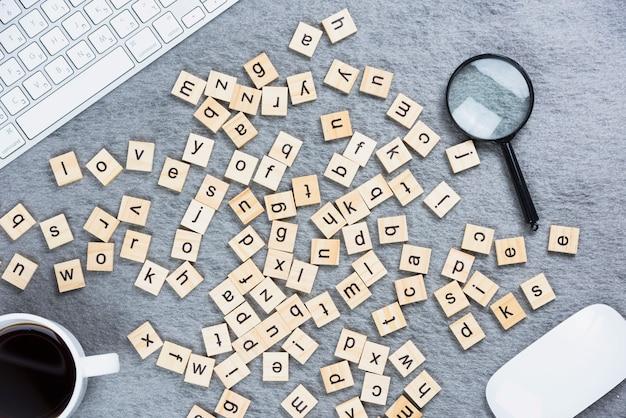 Veel houten blokken van het alfabet met toetsenbord; muis; vergrootglas en een koffiekopje op het bureau