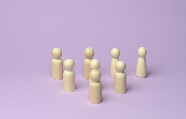 Veel houten figuren van mannen staan op een lila ondergrond, de menigte bij de bijeenkomst