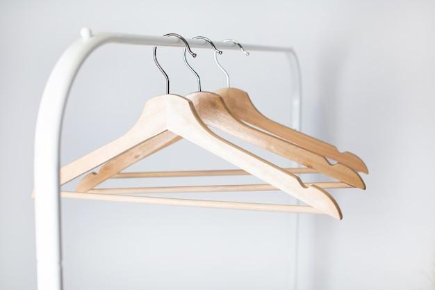 Veel houten hangers aan een staaf, geïsoleerd op een witte muur achtergrond.