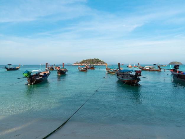 Veel houten longtailboten op blauwe zee bij sunrise-strand op lipe island, satun, thailand, vredig uitzicht op zee, reis- en ontspanningsplaats, traditioneel vervoer