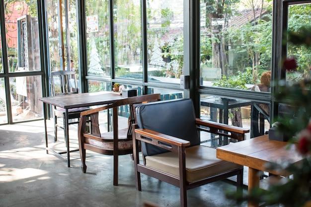 Veel houten tafels en stoelen staan bij ramen in de kamer.