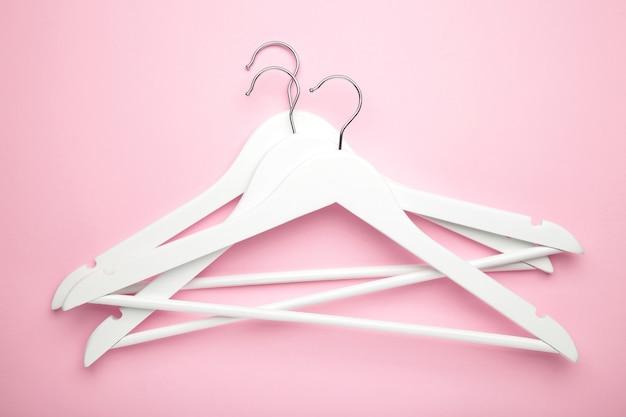 Veel houten witte hangers op roze muur. winkelconcept, lege hanger.