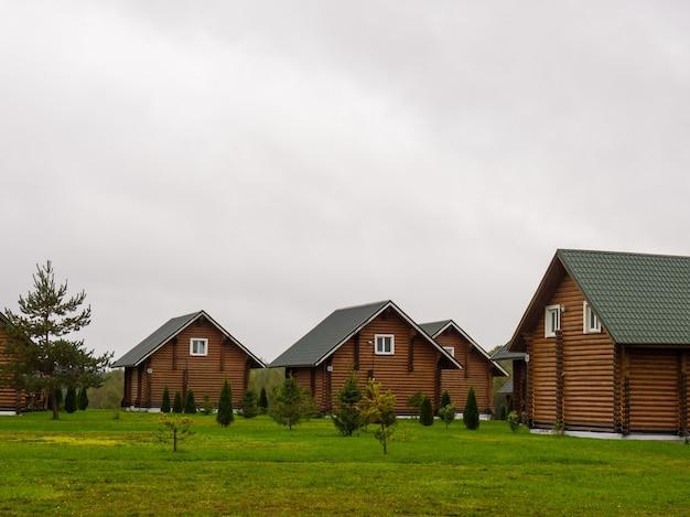 Veel identieke grote blokhutten buiten met een met gras begroeide achtertuin