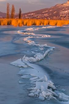 Veel ijsblokken op elkaar in het balatonmeer op de zonsondergang licht