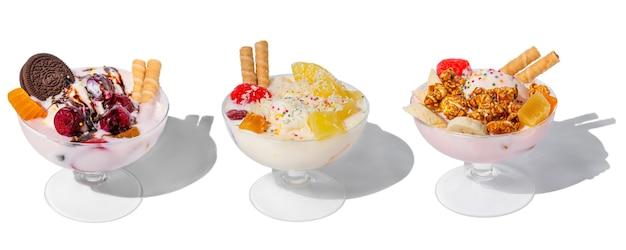Veel ijskommen met verse bevroren yoghurt, fruit, koekjes en kersen geïsoleerd op een witte achtergrond met harde schaduwen
