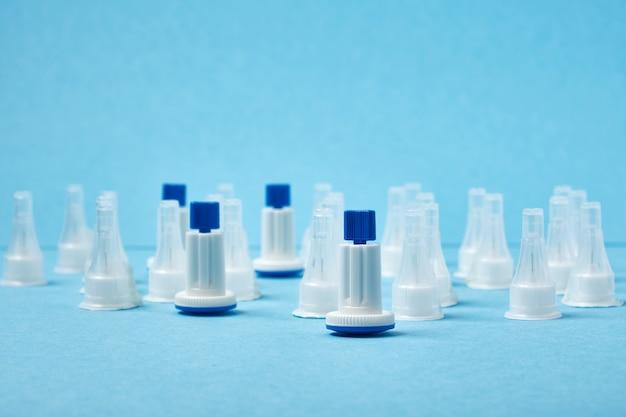 Veel insulinenaalden op een blauwe achtergrond, extra lancetnaalden en spuitinsuline-injectiepennen kopiëren ruimte