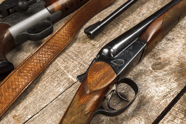 Veel jachtgeweren op verweerd houten oppervlak