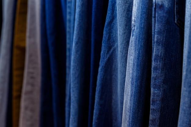 Veel jeans hangen aan het raam op hangers in het winkelcentrum in