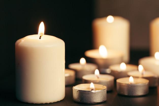 Veel kaarsen branden 's nachts. veel kaarsvlammen gloeien op donker