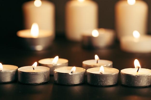 Veel kaarsen branden 's nachts. vele kaarsvlammen gloeien op donkere achtergrond