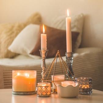 Veel kaarsen met kandelaars op de huisachtergrond