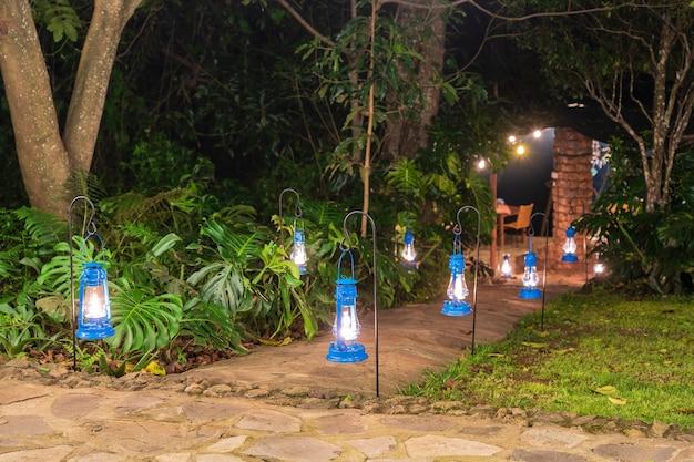 Veel kerosinelampen verlichten de weg in de tropische tuin. tanzania, afrika
