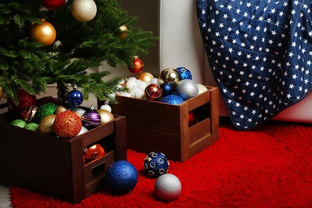 Veel kerstballen op de vloer in feestelijk interieur