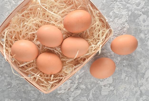 Veel kippeneieren in een mand met stro op een grijze betonnen ondergrond.