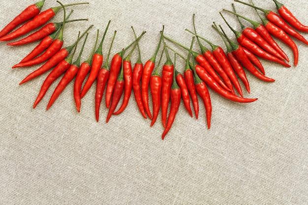 Veel kleine hete rode chilipepersclose-up die in een halve cirkel op natuurlijke fabri liggen