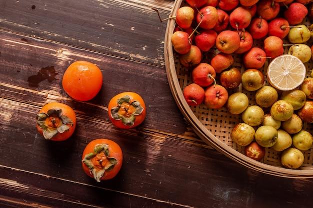 Veel kleuren en soorten fruit liggen op het bord of verspreid op de houten tafel