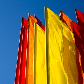 Veel kleurenvlaggen op de wind met heldere blauwe lucht erachter