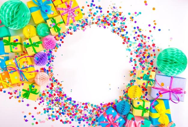 Veel kleurrijke geschenkdozen en kleurrijke confetti op een witte achtergrond. bovenaanzicht