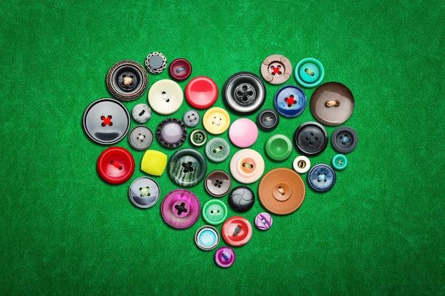 Veel kleurrijke knopen in hartvorm op groene doek