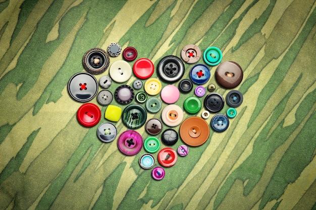 Veel kleurrijke knopen in hartvorm op kaki doek