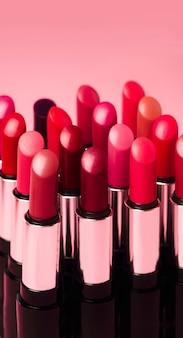 Veel kleurrijke lippenstiften staan op een roze achtergrond