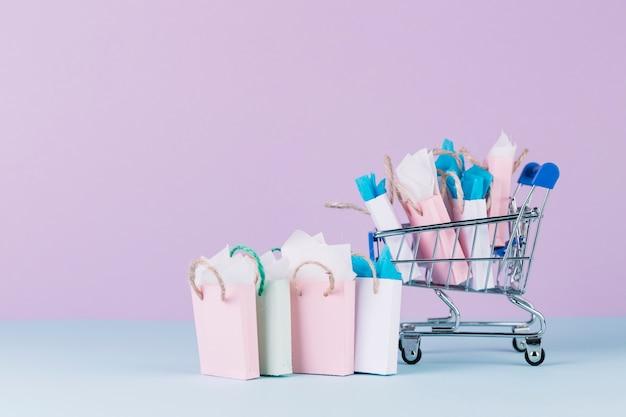 Veel kleurrijke papieren boodschappentassen in winkelwagen