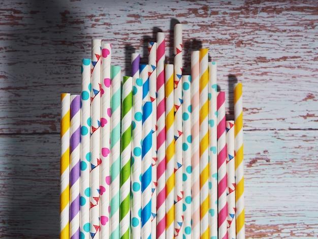 Veel kleurrijke papieren cocktailbuizen liggen als achtergrond.