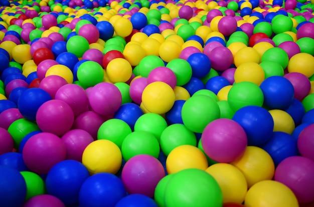 Veel kleurrijke plastic ballen in een kids 'ballpit op een speelplaats. sluit omhoog patroon
