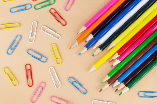 Veel kleurrijke potloden en paperclips, bovenaanzicht