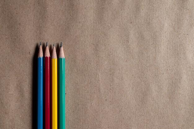 Veel kleurrijke potloden op bruin papier kunnen worden toegepast op ontwerpen.