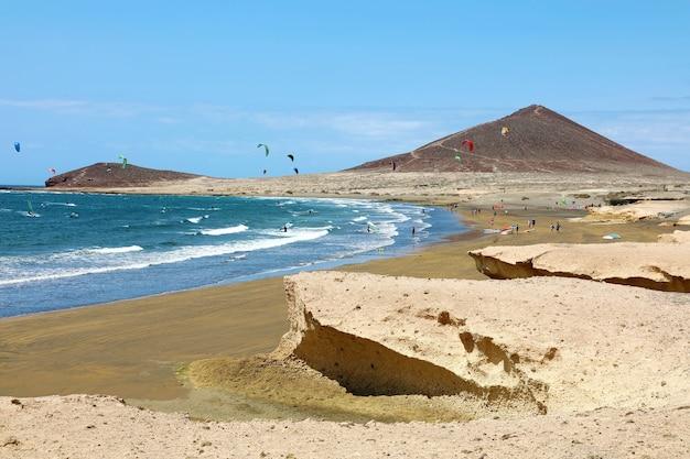 Veel kleurrijke vliegers op strand en kitesurfers die golven berijden en tijdens winderige dag vliegen