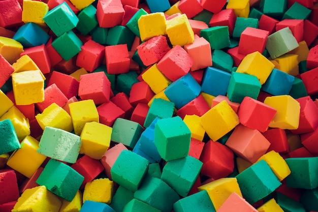 Veel kleurrijke zachte blokken in een kinderzwembad in een speeltuin. heldere veelkleurige zachte kubussen, geometrisch speelgoed. veelkleurige achtergrond.