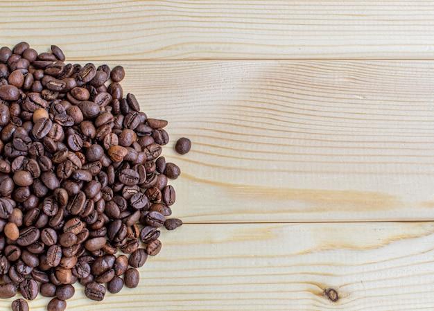 Veel koffiebonen op een houten achtergrond. er is een plaats voor inbreng.